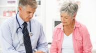 Male doctor talking to mature female patient