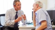 Doctor talking earnestly to patient - a man in his 70s