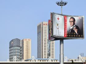 China- skyscrapers and billboard showing man holding glass of baijiu (rice wine)
