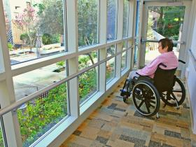 Woman in wheelchair happy looking out of window at garden