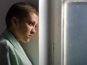 Young woman with shaven hair - cancer patient - looking sad