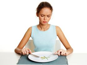 Thin young woman with clean plate