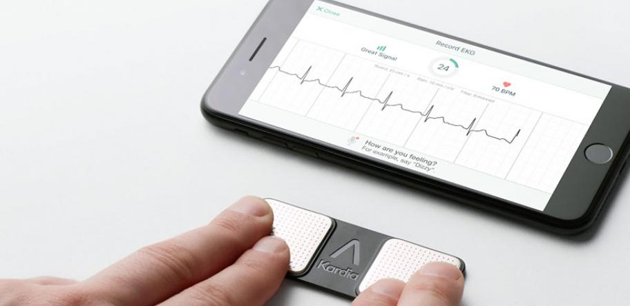 AliveCor monitor with person touching it with 2 fingers from each hand and smartphone showing ECG