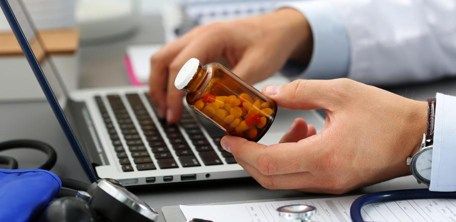 doctor looking up label on pill bottle on his computer