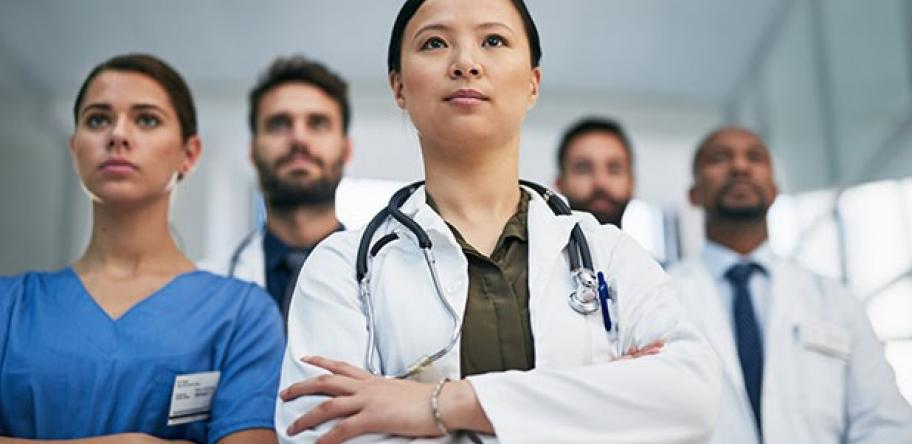 young female hospital doctor with other doctors behind